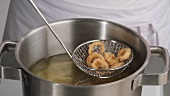 Removing deep-fried calamari from oil