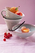 A small bowl and cups with baking ingredients and fruit