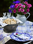 Table set with bread basket and with a bouquet of flowers