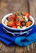 Tomato salad with chickpeas, black olives and pesto dressing