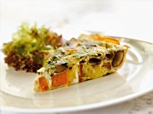 A Slice of Sweet Potato and Gouda Cheese Frittata with a Tossed Salad in a White Plate