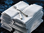 Two Stacks of White Cloth Napkins with a Fork and Knife