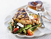 Grilled Swordfish on a Bed of Vegetables with Half a Grilled Peach; Fork and Knife