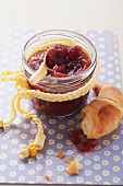 Cranberry jam in jam jar with a piece of croissant