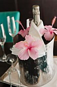 A bottle of champagne in a chiller decorated with hibiscus flowers