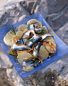 Sardine-potato salad with pine nuts, carrots strips and rosemary