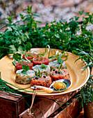 Fischtatar von verschiedenen Fischen mit Kräutern mit rohem Eidotter auf Kräutersauce