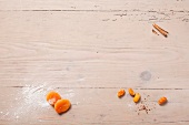Dried apricots, dates and cinnamon stick on wooden background