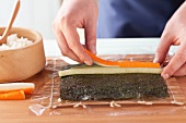 Preparing California rolls: arrange filling on nori