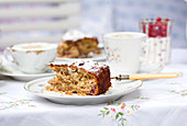 Kuchenstück mit Antikgabel auf altem Blümchenporzellan und passender Tischdecke