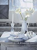 weiße Gedeck, silberne Windlichter, Kerze und Amaryllis auf einem Holztisch