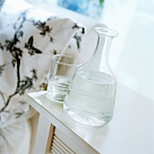 A glass carafe filled with water and glass on a side table