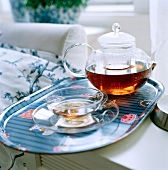 Freshly brewed tea in a glass pot on a tray with a glass cup