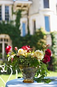 Bouquet of roses on garden table in front of villa
