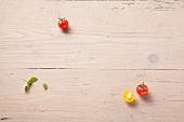 Gelbe und rote Tomaten und Basilikumblätter auf Holzuntergrund