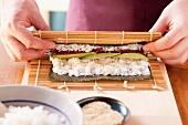 Maki-Sushi zubereiten: Bambusmatte aufrollen