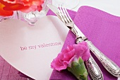 Festive table with carnation and heart-shaped Valentine's Day name card