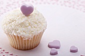 Cupcake with grated coconut and sugar heart