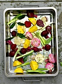 Various types of beetroot and spring onions in a roasting tin