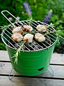Grilled scallops wrapped in bacon with rosemary