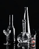 Eiswürfel fällt in Wodkaglas, Weinflasche und Kristallglas
