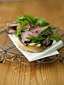 Open faced roll with rump steak, eggplant and rocket