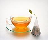 Tea in a glass tea cup next to a tea bag