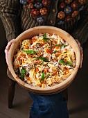 Lady holding a bowl with chirashi sushi