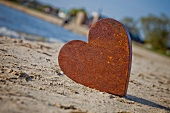 Rusty metal heart on the seashore