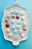 Pastel colored meringues on a wooden tray (top view)