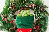 Brussels sprouts in a stocking in front of a Christmas wreath