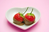 Two chocolate-dipped strawberries in a heart-shaped dish