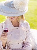 Lady wearing a hat drinking a glass of red wine