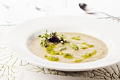Bowl of Creamy Artichoke Soup with Pesto and Fresh Purple Basil and Lemon Basil