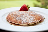 Pancakes with Powdered Sugar and a Strawberry; Outdoors