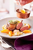 Fried pigeon breast with orange sauce and ravioli
