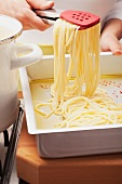 Putting spaghetti on a baking tray with olive oil