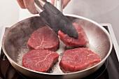 Frying steaks in a pan