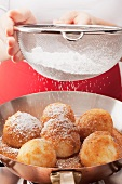 Dusting apricot dumplings with icing sugar