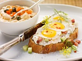 Open-faced sandwich of sour cream and vegetable spread with quail's eggs and small bowl of Liptauer (spicy cheese spread)