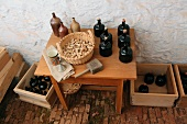 Various bottles made of clay and black ceramic next to a basket of corks on a wooden table