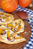 Tarte flambée with pumpkin, red onions and goat's cream cheese