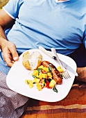A man holding a plate of grilled potatoes, salad and sausage