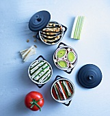 Four different vegetable dishes in miniature cocotte pots