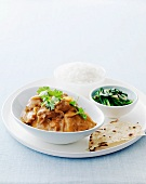 Butter chicken in mustard sauce with spinach, rice and flatbread