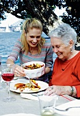 A granddaughter and a grandmother having lunch