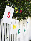 Pieces of paper spelling the word SWEET hanging on a washing line