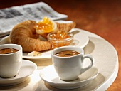 Two cups of espresso with a croissant and jam