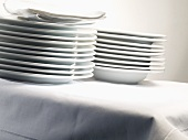 Stacked porcelain plates and linen napkins on table