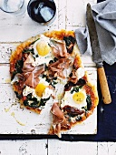 A pizza topped with spinach, dried tomatoes, ham and fried eggs